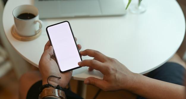Cortada vista das mãos do homem segurando o smartphone de tela em branco