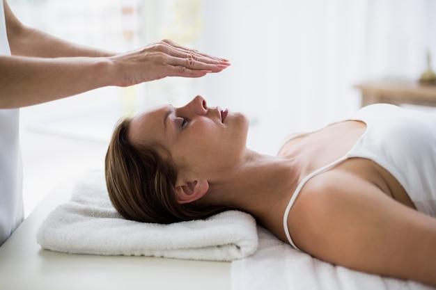 Cortadas as mãos do terapeuta realizando reiki na mulher