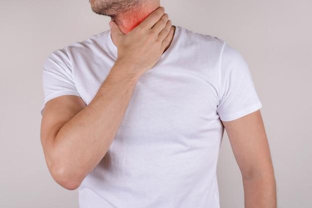 Cortado close up foto estúdio retrato de barbudo com barba por fazer infeliz triste chateado viril masculino cara bonito segurando tocando doloroso pescoço vestir camiseta branca isolado fundo cinza cópia espaço