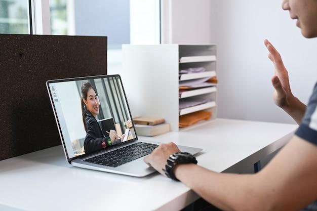 Cortado de um homem usando o computador laptop, fazendo videochamada com seu colega enquanto está sentado em seu escritório em casa moderno.
