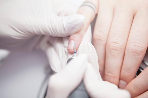 Cortado em close da manicure usando broca de unha nas cutículas da cliente