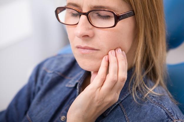 Cortado em close de uma mulher com dor de dente