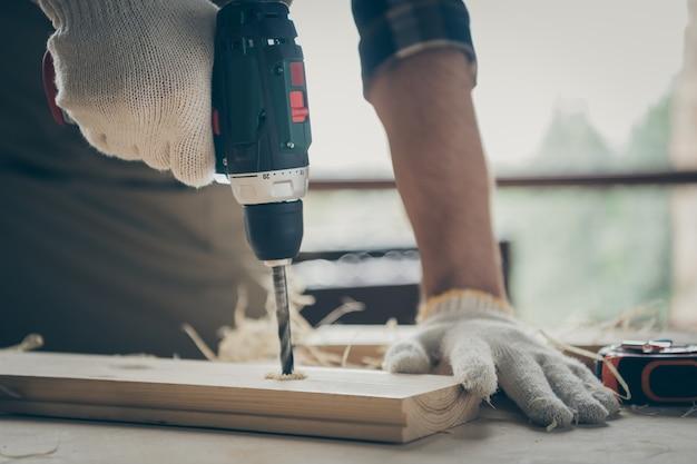 Cortado em close-up de suas mãos, especialista em reparador experiente, especialista em criação de novo projeto de loja de presentes, furo de perfuração de decoração de casa inicial usando dispositivo elétrico na mesa