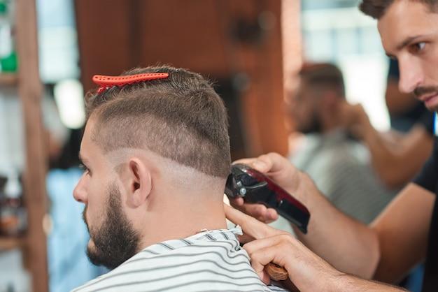 Cortado em close up de um barbeiro profissional trabalhando em sua barbearia, cortando o cabelo de seu cliente.