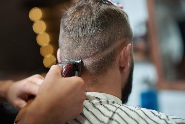 Cortado em close up de um homem recebendo seu cabelo estilizado por um barbeiro profissional na barbearia.