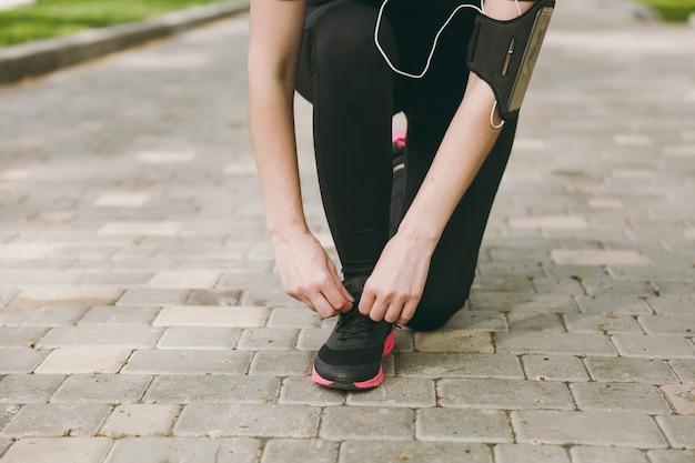 Cortado perto de mãos de mulher amarrando cadarços em tênis preto e rosa em corrida ou treinamento em caminho ao ar livre
