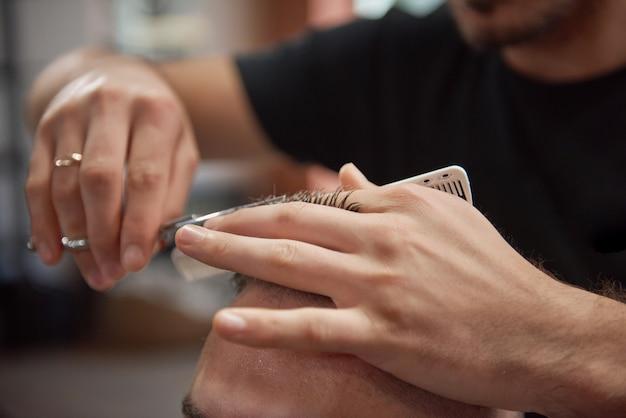 Cortado perto de um barbeiro profissional, usando uma tesoura e um pente, enquanto cortava o cabelo de sua cliente.