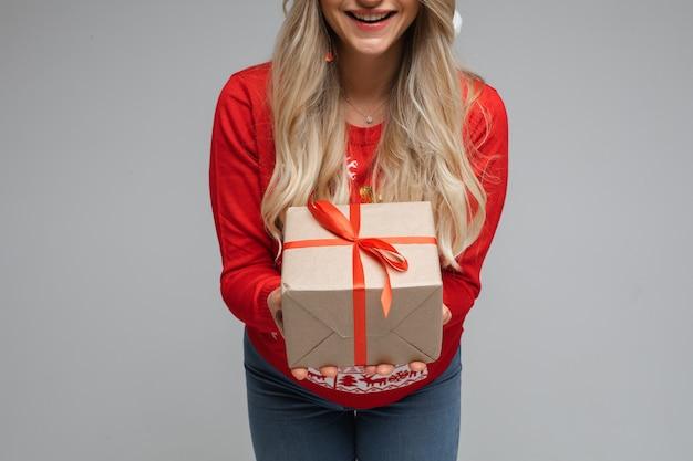 Cortado perto de uma garota loira de cabelos compridos sorridente, de suéter vermelho, dando presentes em fundo cinza.