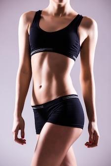 Cortado perto do corpo de uma mulher em forma usando shorts e blusa esporte mostrando uma bela barriga e abdominais