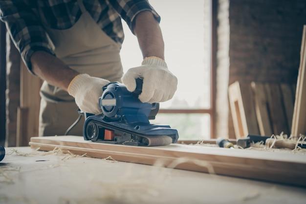 Cortado perto, homem trabalhando com lixa, cercado por limalhas processando bloco de madeira com as mãos nas luvas
