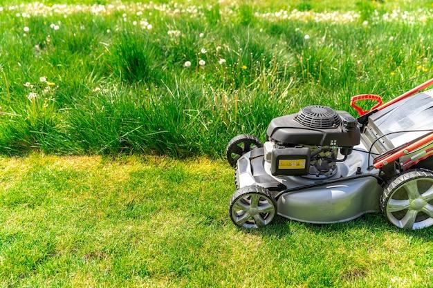 Cortador a motor para cortar a grama ao lado da casa da família