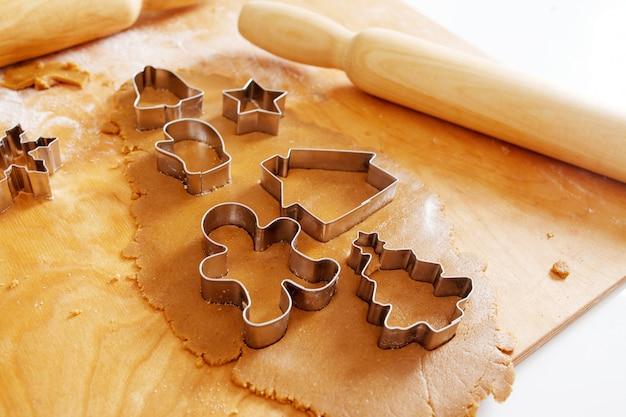 Cortador de biscoito de árvore de gengibre de natal na massa com rolo, quadro completo. comida festiva, processo de cozimento, culinária familiar, conceito de tradições de natal e ano novo.