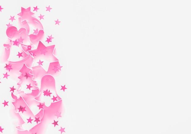 Cortador de biscoito rosa e confetes estrela fronteira festiva de natal minimalista com copyspace