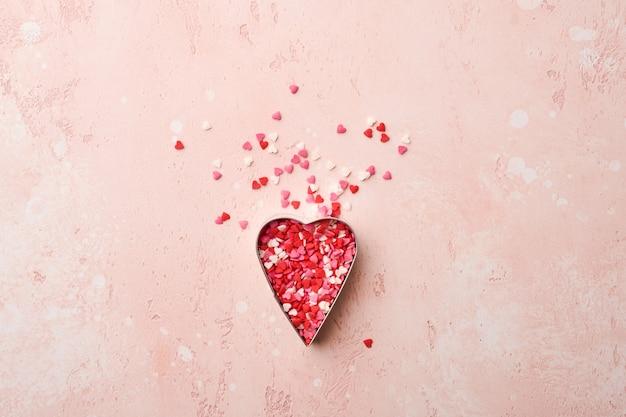Cortador de biscoitos em forma de coração com doces multicoloridos espalhados para assar na mesa-de-rosa.