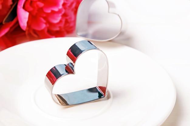 Cortador de biscoitos em forma de coração em close-up de placa branca. conceito de dia dos namorados.