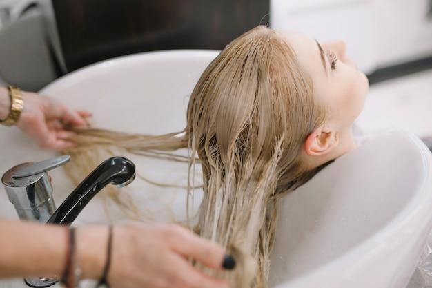 Cortador de cabeleireiro que lava o cabelo do cliente
