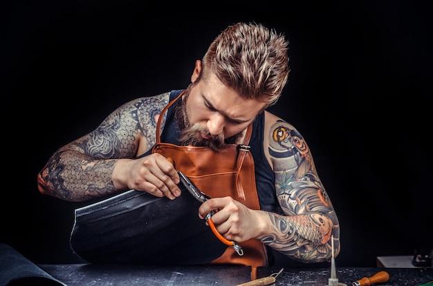 Cortador de couro trabalha com artigos de couro na curtume.