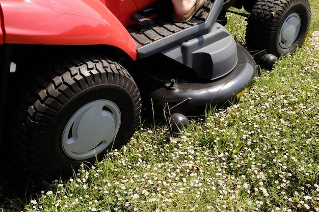 Cortador de grama com algumas flores na frente