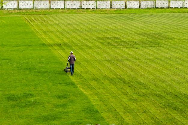 Cortador de grama corta grama no campo de futebol enquanto trabalha