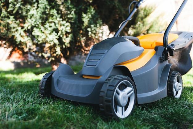 Cortador de grama elétrico em um gramado no jardim Foto Premium