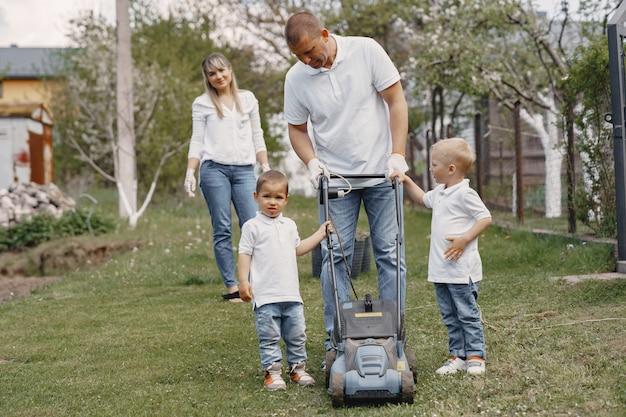 Cortador de grama homem trabalhando no quintal com filhos