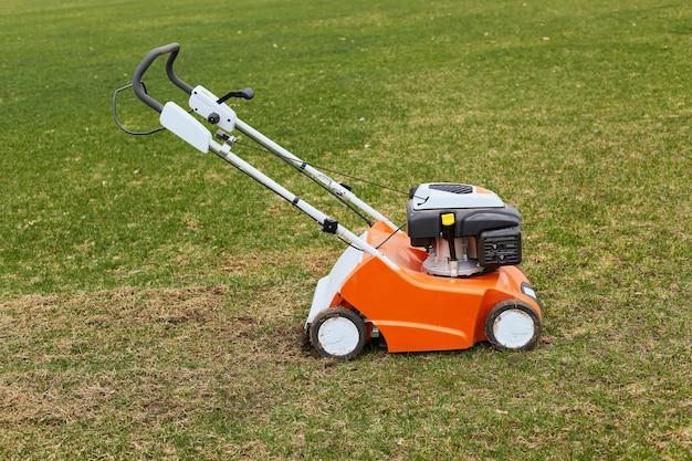 Cortador de grama laranja parado no chão na grama verde