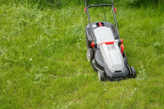 Cortador de grama na grama verde no jardim. equipamento cortador de grama. ferramenta de trabalho de cuidado de jardineiro de sega.