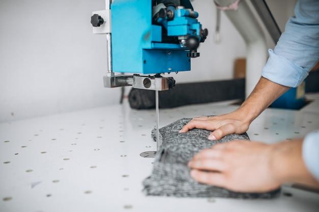 Cortador de homem em uma fábrica de costura, mãos masculinas close-up