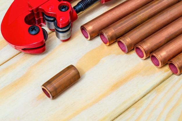 Cortador de tubos vermelho e tubos de cobre com conectores para reparos de encanamento em placas de madeira vintage close-up