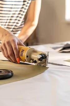 Cortador elétrico para cortar close up de têxteis de trabalho de mão feminina com tecido na sala de estúdio do atelier