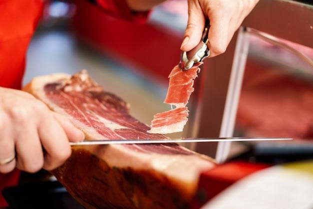 Cortador profissional esculpindo fatias de um presunto serrano com osso