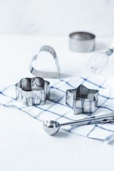 Cortadores de biscoito, acessórios de cozinha em uma mesa de cozinha branca