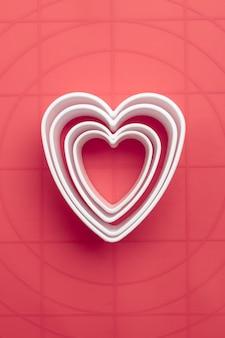 Cortadores de biscoito de símbolo de coração branco em fundo coral