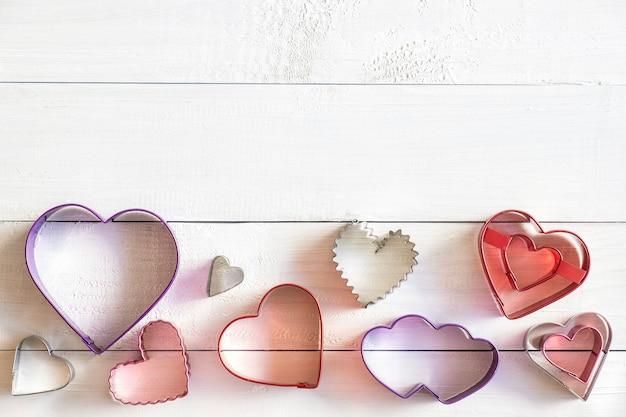 Cortadores de biscoitos em forma de coração em fundo branco de madeira, vista superior, espaço de cópia
