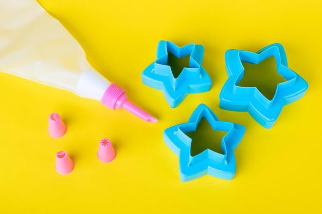 Cortadores de biscoitos em forma de estrela. ferramentas para decoração de bolos, saco de confeitar com bicos em uma parede amarela para decoração de bolos. conceito de cozinha de confeitaria com creme.