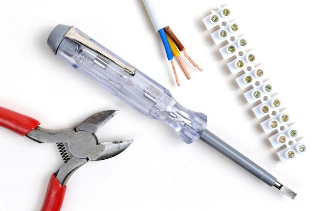 Cortadores de fio, fio descascado, chave de fenda testadora e bloco de terminais. sobre um fundo branco, vista superior.