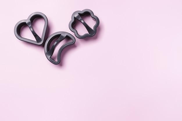Cortadores de moldes de biscoito em fundo rosa com espaço em branco para seu anúncio.