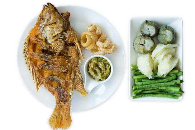 Cortados de peixe de tilápia vermelha frita e molho de pimenta verde tailandês do norte, misture com vegetais escaldados, coma com junta de porco frita e branca isolada.