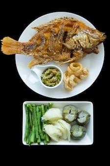 Cortados de peixe de tilápia vermelha frita e molho de pimenta verde tailandês do norte, misture com vegetais escaldados, coma com pork knuckle preto frito isolado.