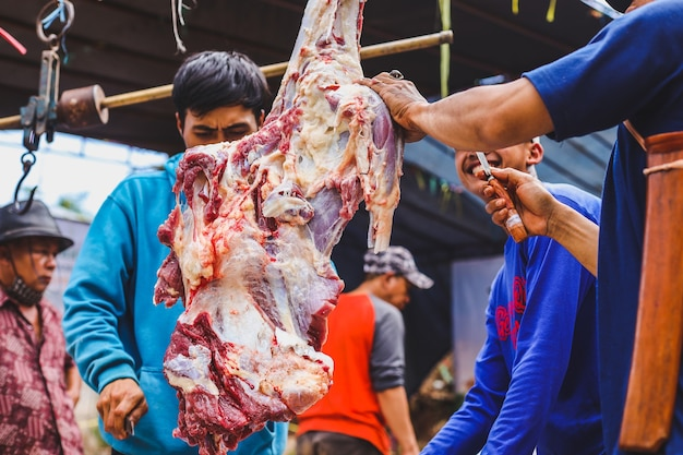 Cortando a carne de uma cabra para ser distribuída aos muçulmanos durante o eid aladha
