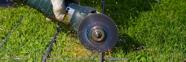Cortando a rede do metal com o moedor na grama verde. faíscas com materiais de contato. trabalhador lá fora, corte a rede de aço. processo com rebarbadora.
