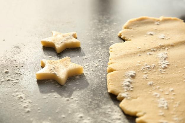 Cortando biscoitos da massa crua na mesa