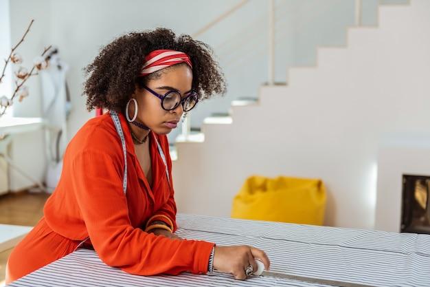 Cortando o tecido branco. mulher afro-americana brilhante usando um pedaço de giz para marcar tecidos para cortá-los