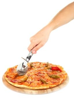 Cortando saborosa pizza de pepperoni em um suporte de madeira isolado no branco