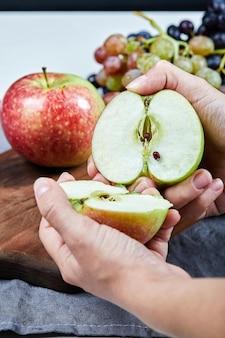 Cortando uma maçã em duas metades e cacho de uvas na placa de madeira.