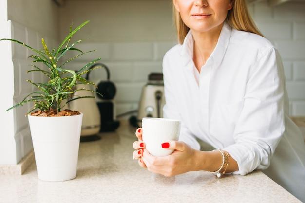Cortar a foto da mulher loira encantadora, com longos cabelos louros na camisa branca com uma xícara de chá em mãos na cozinha brilhante antes do dia útil