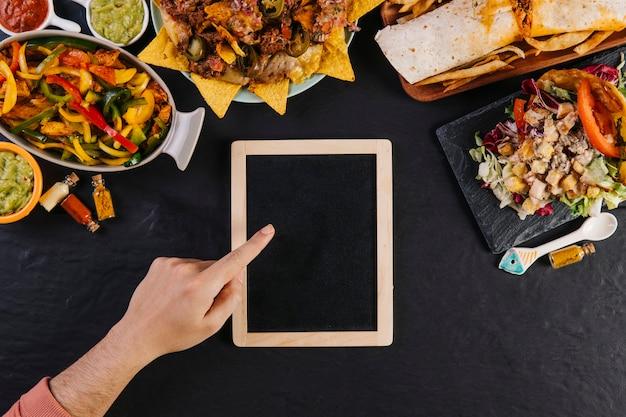 Cortar a mão apontando no quadro-negro perto da comida