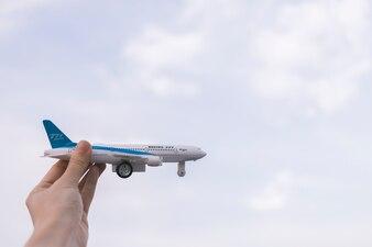 Cortar a mão segurando o avião de brinquedo