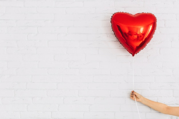 Cortar a mão segurando o balão do coração