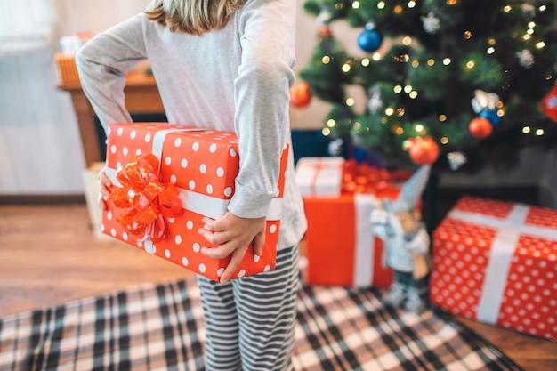 Cortar a vista da menina pequena em pé e segurando a caixa vermelha nas costas